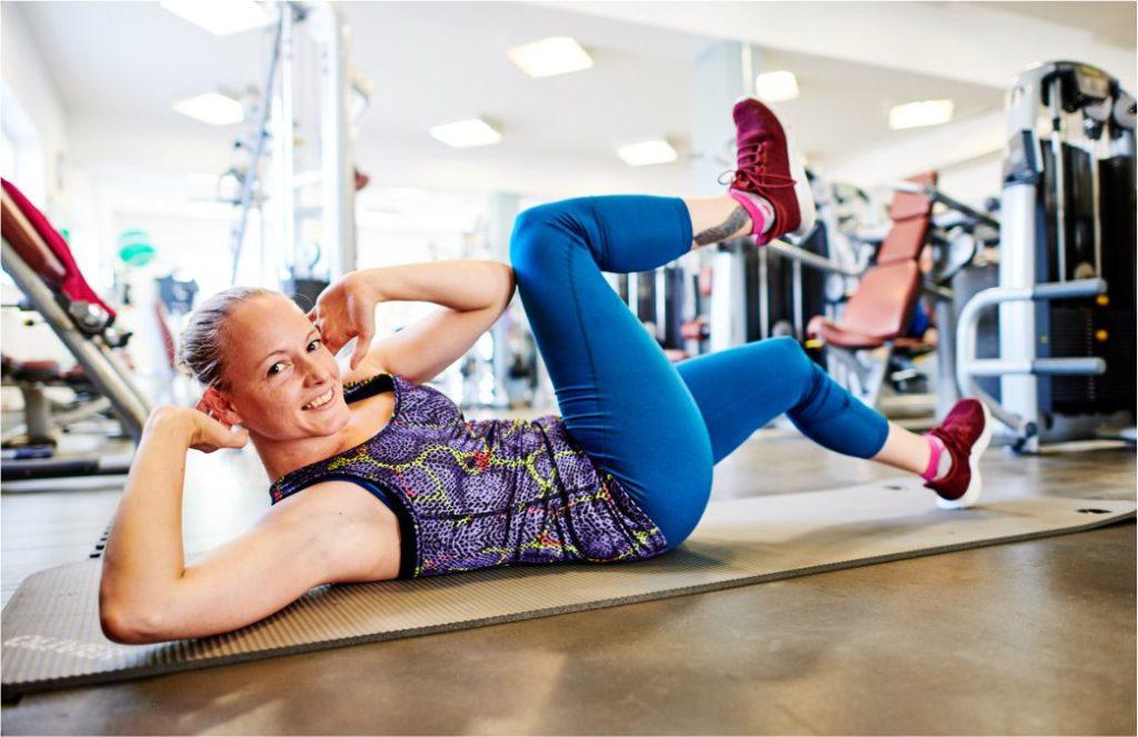 Diagonales Bauchtraining Frau im Fitnessstudio